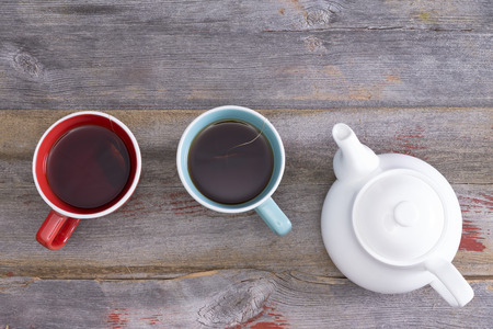 Tea for two with two ceramic cups of freshly brewed black tea standing on a weathered rustic wooden table alongside a teapot, overhead view with copyspace