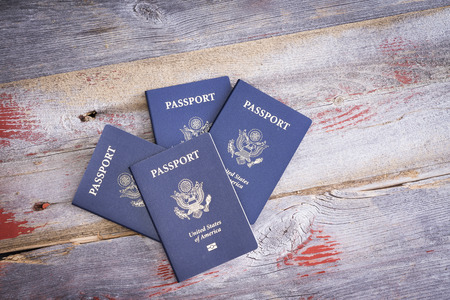 View from above of four United States passports on a rustic wooden table conceptual of family or group travel, with copyspace