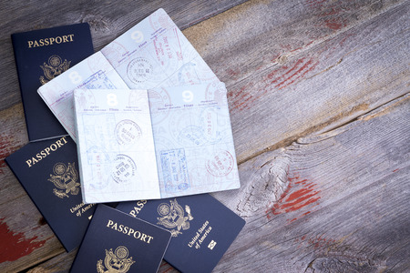 American passports lying on a rustic wooden table open to reveal hand stamps from customs officials on border control applied during traveling abroad