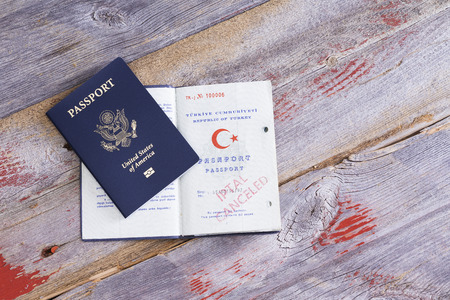 An American and Turkish passport lying on an old wooden table with the Turkish passport opened to reveal a cancelled hand stamp conceptual of immigration and changing citizenship
