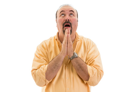 religious clothing: Middle-aged man praying to heaven for help clasping his hands in fervent supplication as he beseeches Divine intervention, part of a series on body language, isolated on white Stock Photo