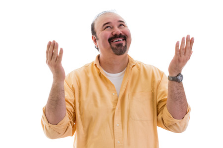 Happy middle-aged man giving thanks to God for a successful outcome smiling and raising his hands with a smile in thanksgiving, part of a series on body language, isolated on white