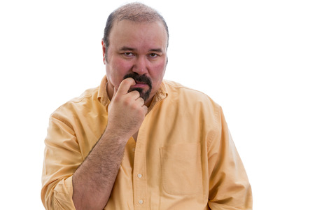 Thoughtful man chewing his finger as he debates a problem staring straight ahead with a serious expression, part of a series on body language, isolated on white Reklamní fotografie