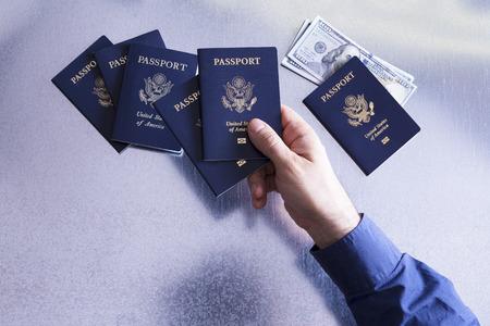 guia turistico: Vista de arriba de la mano de un hombre de la clasificaci�n y el control de los pasaportes de los Estados Unidos con billetes de d�lares escondido bajo uno que representa a un hombre de familia, funcionario de aduanas o de gu�a tur�stico con el dinero para el pago de una cuota o de soborno