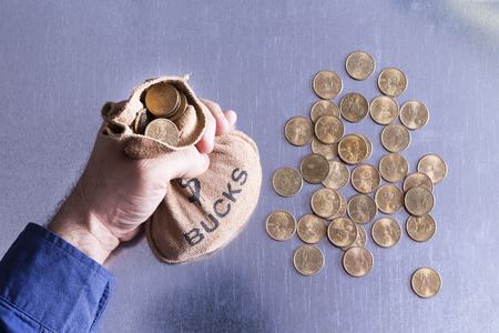 Man holding a money bag full to overflowing of Bucks with American dollar coins lying strewn on the table below in a concept of greed, wealth, investment or gambling at a casino, overhead view Editöryel