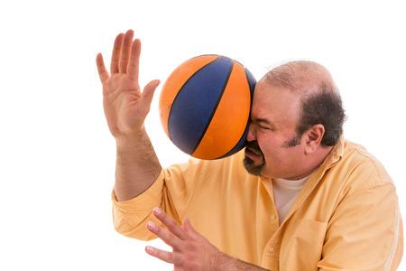 Hombre de mediana edad calvo con un deporte jugando perilla ser golpeado por una pelota de baloncesto con fuerza en la cara cuando se pierde una captura o un accidente inesperado para un espectador, en blanco Foto de archivo