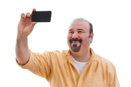 Gelukkig man die een zelfportret of selfie op zijn mobiele telefoon te sturen naar zijn vrienden op de sociale media netwerk met de telefoon in zijn hand als hij vormt, geïsoleerd op wit Stockfoto
