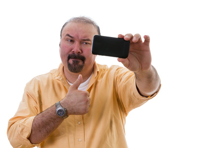 Middle-aged man with a goatee standing posing while taking a self portrait on his mobile as he gives a thumbs up of approval with a frown as though reluctant to do so, isolated on white photo