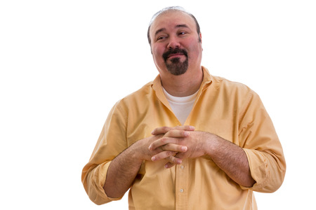 Happy overweight middle-aged man with a goatee clasping his hands over his chest and glancing sideways with a complacent expression and pleased smile, on white