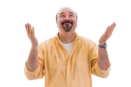 agradecimiento: Feliz hombre de mediana edad de pie la celebración de un éxito o solución levantando las manos al cielo en agradecimiento y alabanza con una radiante sonrisa, sobre fondo blanco