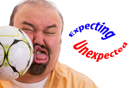 Fun picture of a middle-aged man with a goatee having the wind knocked out of him by the unexpected force of a soccer ball connecting with his face and the text expecting - unexpected, on white 版權商用圖片 - 27162459