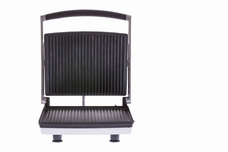 Low angle frontal view of an open electrical panini press or grill with cast iron teflon-coated plates isolated on white photo