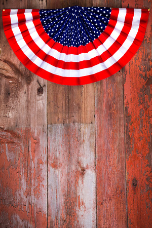 vertical format: Independence Day patriotic rosette to commemmorate the signing of the Declaration of Independence on the 4th July lying on rustic wooden boards with plenty of copyspace in vertical format