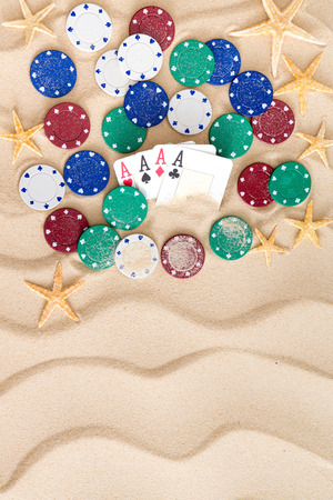 4 of a kind: Four aces surrounded by poker chips and scattered starfish on golden beach sand with a decorative wavy pattern and copyspace