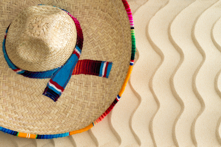 View from above of a Mexican straw sombrero with a colorful decorative ribbon lying on golden wavy beach sand with a ripple effect and copyspace in the warm summer sun photo