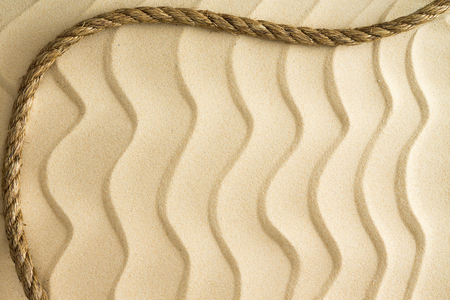 ripple effect: Nautical background of wavy golden beach sand with a ripple effect with a decorative curving rope border and copyspace