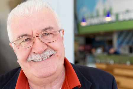 charismatic: Close up portrait of the face of an attractive friendly sincere senior grey-haired man in glasses with a moustache looking directly into the lens with a charming smile