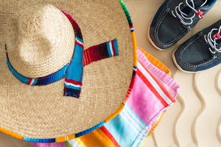 Wide brimmed straw sombrero lying on a colorful striped beach towel with a pair of sneakers on tropical beach sand with a decorative wavy pattern, view from above conceptual of summer holidays photo