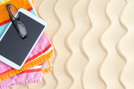 blank tablet: Tablet and glasses on a colorful beach towel lying on golden beach sand with a ridged wavy pattern in the hot summer sunshine for a relaxing day at the seaside