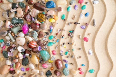 pietre preziose: Ciottoli, pietre preziose e conchiglie sparse in una disposizione decorativa tropicale sulla spiaggia di sabbia dorata con un increspato ondulato disegno ondulato in uno sfondo nautica ornamentali
