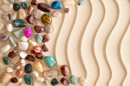 Arrangement of waterworn pebbles and colorful tumbled polished gemstones on golden beach sand with an undulating wavy pattern and copyspace