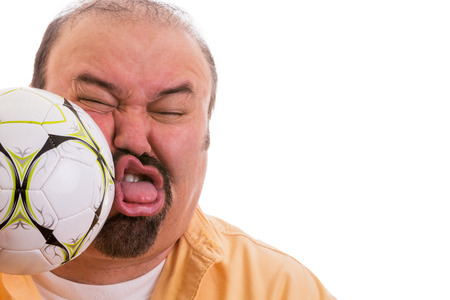 Fun picture of a middle-aged man with a goatee having the wind knocked out of him by the unexpected force of a soccer ball connecting with his face