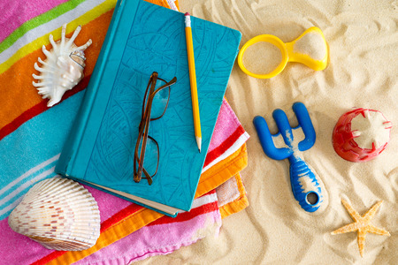 mementos: Book and reading glasses on a colorful beach towel on a sandy beach with plastic toys, a starfish and seashells with a parent reading as the children collect mementos on a tropical summer vacation Stock Photo