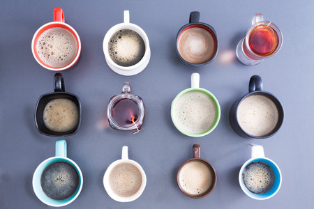 teatime: Time for a coffee break or teatime with a neat line up of dfifferent mugs and glasses containing freshly brewed coffee and tea for a daily dose of caffeine to energize your day, view from above Stock Photo