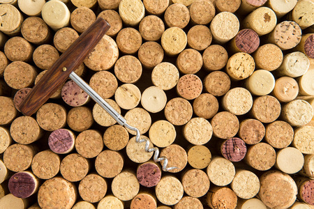 Background texture of neatly arranged corks and calassic wine bottle opener wine packed tightly together with their tops facing up to the camera forming a circular pattern photo