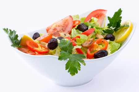 ceramic bottle: Fresh Mediterranean salad with black olives, tomatoes, parsley, lemon, peppers, lettuce seasoned with olive oil, lemon, and oregano Stock Photo
