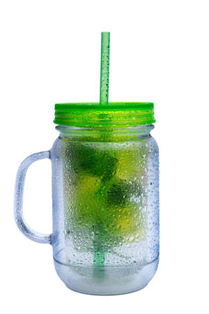 chilled: Glass jar of healthy iced water with mint and lemons frosted on the outside by the chilled water and served with a straw for a refreshing drink Stock Photo