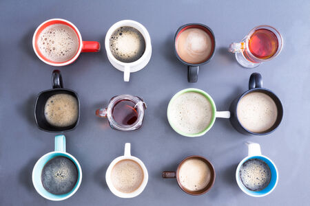 break: Time for a coffee break or teatime for office with a neat line up of dfifferent mugs handles looking diffrent directions, freshly brewed foamy coffee and teas for a daily dose of caffeine to energize your day, view from above