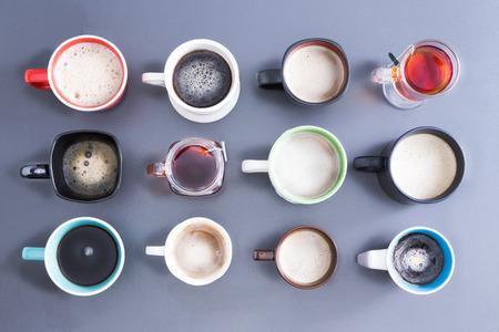 カフェインの 12 の異なるカップ、マグカップ、ホットの新鮮な茶と灰色の上にコーヒーをいっぱいグラスのきちんとした配置のオーバーヘッドを見
