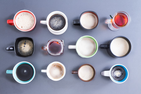 Conceptual image depicting the Time for your daily dose of caffeine with an overhead view of a neat arrangement of twelve different cups, mugs and glasses filled with hot fresh tea and coffee on grey Stock Photo