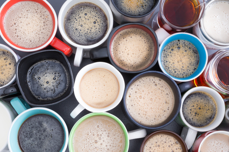 energising: Background with a view from above of closely packed assorted mugs full of fresh hot coffee covered in froth