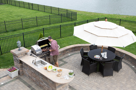man outdoors: High angle view of a man cooking meat on a gas BBQ standing in the sunshine on a paved outdoor patio at the summer kitchen preparing for guests with a table and chairs with a garden umbrella alongside