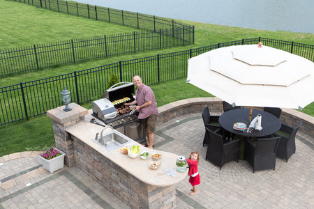 Father and daughter preparing a barbecue at an outdoor summer kitchen on a paved patio with a garden umbrella, table and chairs as they grill the meat on the gas BBQ waiting for guests to arrive