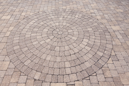 Architectural Background Of An Ornamental Pattern In Outdoor Patio Paving  With Bricks Arranged In A Circular
