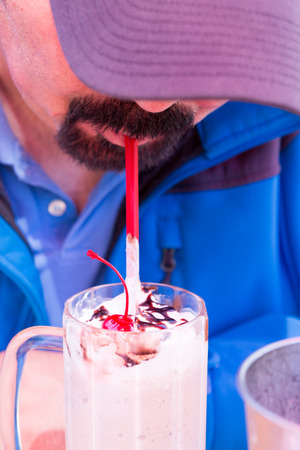 Man with a goatee beard bending forwards in a peak cap drinking a delicious creamy milkshake topped with a cherry and chocolate through a straw photo