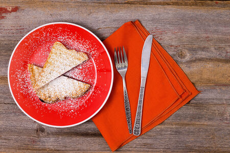 Traditional Italian panini with blueberry jam sprinkled with powdered sugar and served on a colorful orange plate with a matching napkin in a restaurant, overhead view on a wooden table Reklamní fotografie