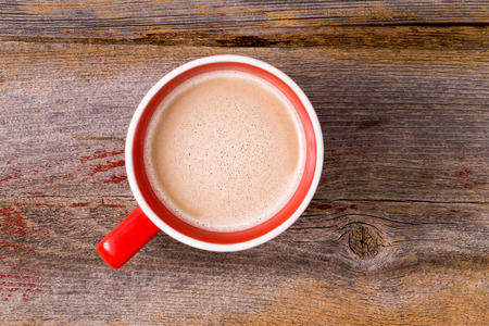 brew house: Orange ceramic mug full of fresh hot latte morning coffee topped with a milky froth