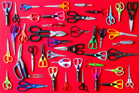 Display of multiple different pairs of domestic scissors on red conceptual of scissors for everyone and for every different task, overhead view photo