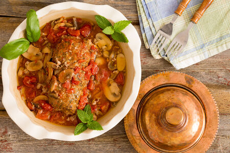 meatloaf: Sliced savory meatloaf with mushrooms and vegetables served in a casserole on a rustic wooden table with grungy peeling red paint, overhead view, copy space on the left Stock Photo