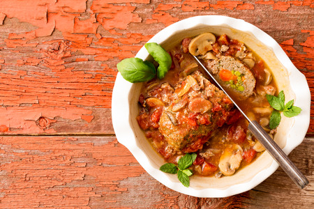 Sliced savory meatloaf with mushrooms and vegetables served in a casserole on a rustic wooden table with grungy peeling red paint, overhead view, copy space on the left Stock Photo