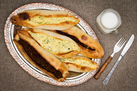glass topped: Turkish pide, a traditional unleavened flatbread , topped with ground beef and cheese and served with a glass of ayran, a Turkish salted yoghurt drink, high angle view