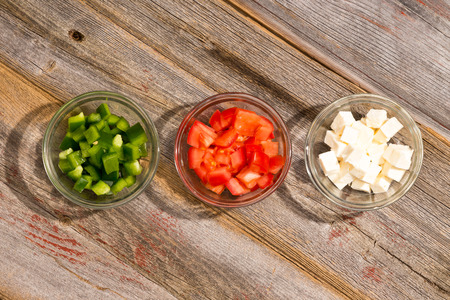 Ingredients for a simple healthy Greek salad arranged in individual glass bowls with diced green bell pepper, tomato and cubes of goats milk feta cheese lined up ready for use on a rustic wooden table