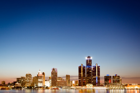 Detroit, Michigan skyline at twilight with the illuminated lights of the waterfront buildings in the CBD reflected in the water of the Detroit River photo