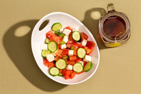 Simple fresh salad with feta cheese, cucumbers, ripe red tomato and green bell pepper served with a glass cup of freshly brewed hot tea, overhead view on a beige cotton cloth in sunshine with shadow photo