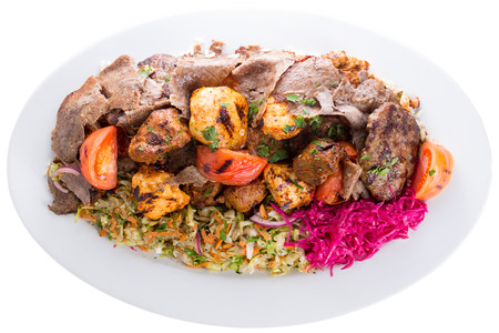 Plate of delicious grilled mixed shish kebabs with beef and chicken served with fresh greens, red cabbage and tomato and lamb kofte isolated on white