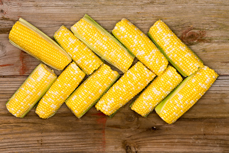 mealie: Fresh yellow corn on the cob arranged in a pointer on a rustic wooden table Stock Photo